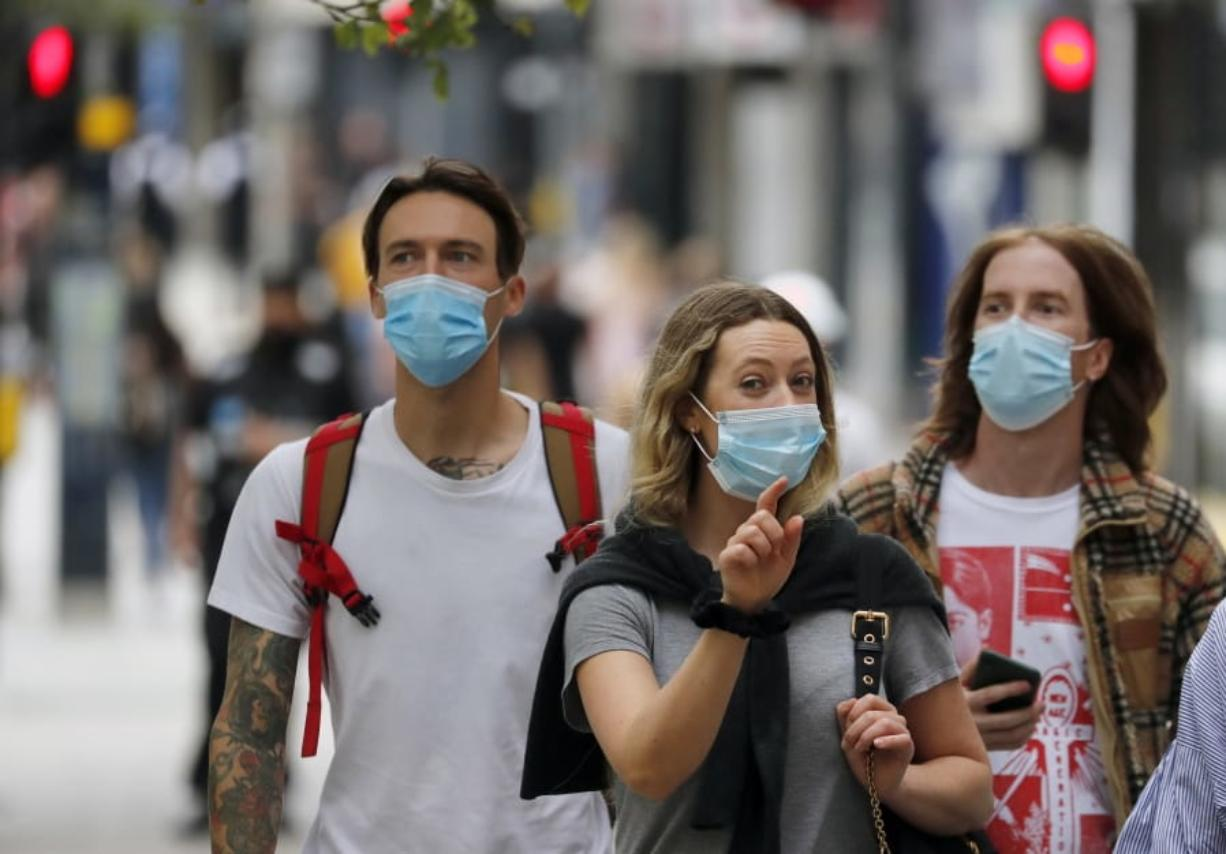 Shoppers wearing protective face masks walk along Oxford Street in London, Tuesday, July 14, 2020.Britain's government is demanding people wear face coverings in shops as it has sought to clarify its message after weeks of prevarication amid the COVID-19 pandemic.