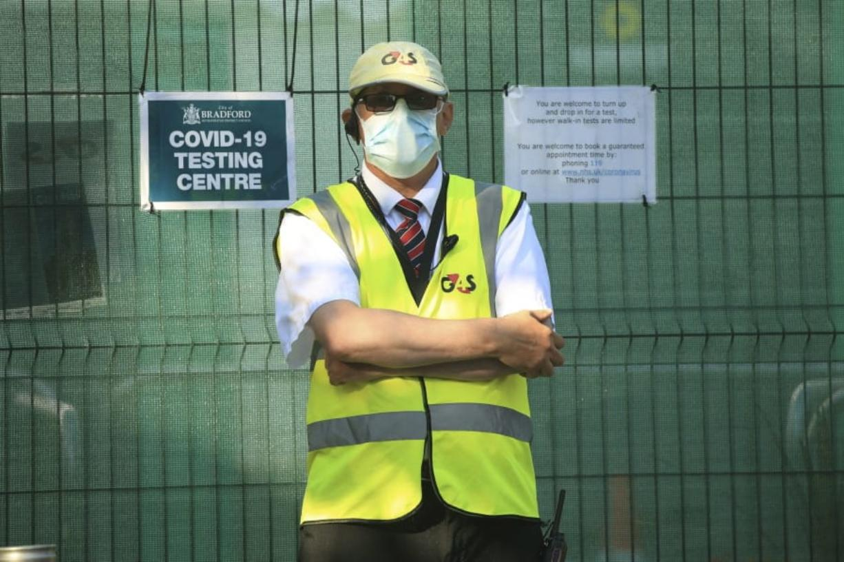 A security guard outside a Covid-19 testing centre, in Bradford, West Yorkshire, England, Friday July 31, 2020. Britain's health secretary has defended a decision to reimpose restrictions on social life in a swath of northern England, saying it was important to keep ahead of the spread of COVID-19. Under the new restrictions, people from different households in Greater Manchester, England's second largest metropolitan area, have been asked to not meet indoors. The same orders applies to the surrounding areas of Lancashire and West Yorkshire counties.