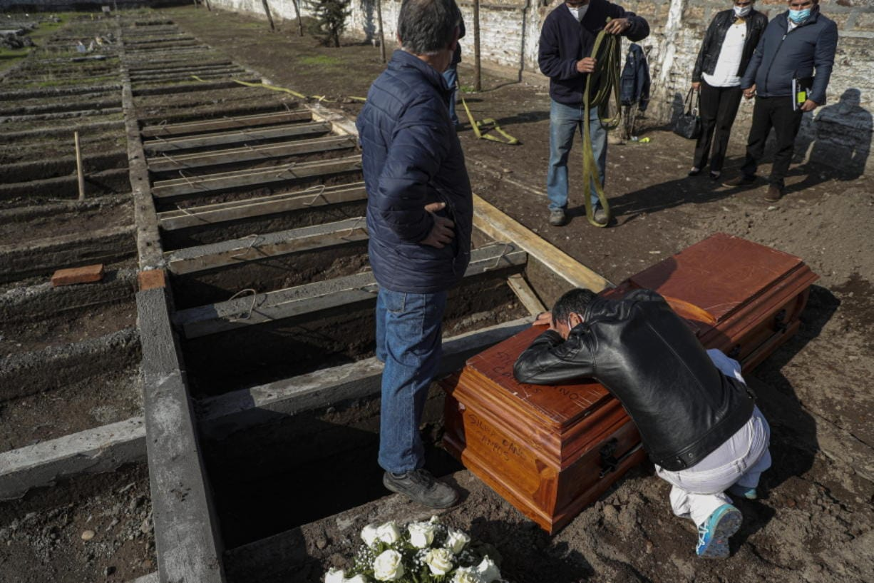 Peruvian migrant Jose Collantes grieves as he cries on the coffin that contains the remains of his wife Silvia Cano, who died due to COVID-19 complications, according to Collantes, at a Catholic cemetery in Santiago, Chile, Friday, July 3, 2020.