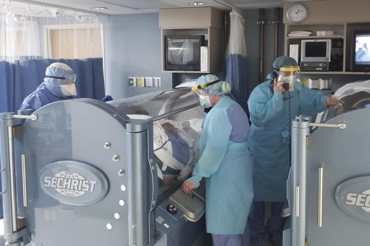 In this April 2020 photo provided by The Wound Treatment Center, two COVID-19 patients are treated in hyperbaric chambers at a hospital in Opelousas, La. The therapy involves delivering 100% oxygen straight to patients inside a pressurized chamber.