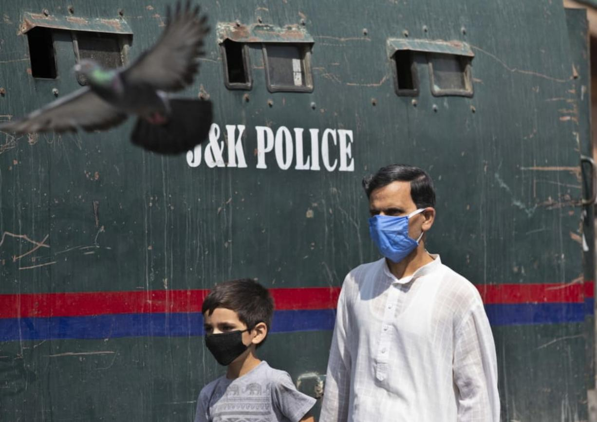 A Kashmiri man and a child wearing masks walk past a parked armored police vehicle in Srinagar, Indian controlled Kashmir, Monday, July 13, 2020. Authorities reimposed lockdown on Monday in parts of Indian-controlled Kashmir, including the region's main city, following surge in coronavirus cases.