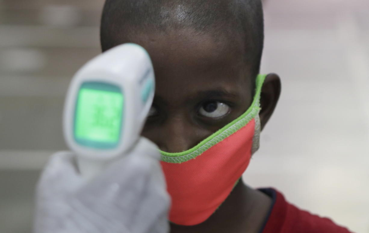 A health worker checks the body temperature of a boy at a medical camp to screen residents for COVID-19 symptoms in Mumbai, India, Friday, July 17, 2020. India crossed 1 million coronavirus cases on Friday, third only to the United States and Brazil, prompting concerns about its readiness to confront an inevitable surge that could overwhelm hospitals and test the country's feeble health care system.