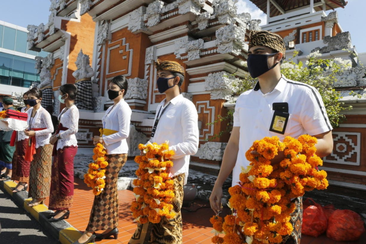 Airport officers wearing face masks line up as they hold flowers to welcome passengers at Bali airport, Indonesia on Friday, July 31, 2020. Indonesia's resort island of Bali reopened for domestic tourists after months of lockdown due to a new coronavirus.
