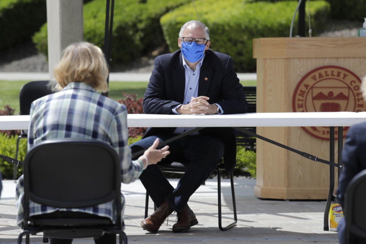 Washington state Gov. Jay Inslee listens at an outdoor round table meeting with leaders in local government, health care and business talking about the high rate of coronavirus cases in the area at Yakima Valley College Tuesday, June 16, 2020, in Yakima, Wash. Inslee met to discuss the impact of the COVID-19 pandemic in the area, which has one of the highest rates of infection in the state.