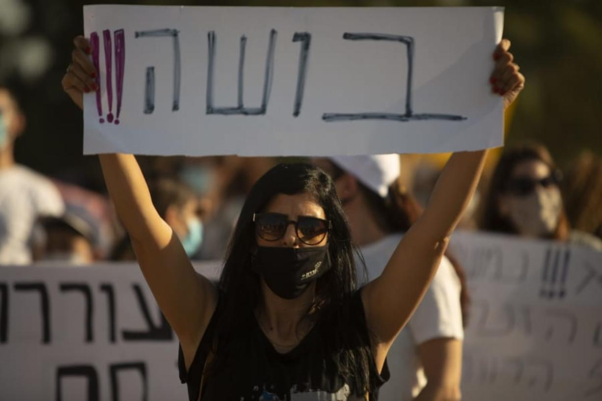 "An Israeli social worker holds a sign in Hebrew that reads, ""shame,"" during a protest against the economic situation in the central Israeli town of Kfar Ahim, Thursday, July 9, 2020. With a new outbreak of coronavirus devastating Israel's economy, one of Prime Minister Benjamin Netanyahu's closest confidants was dispatched on to a TV studio on a recent day to calm the nerves of a jittery nation."