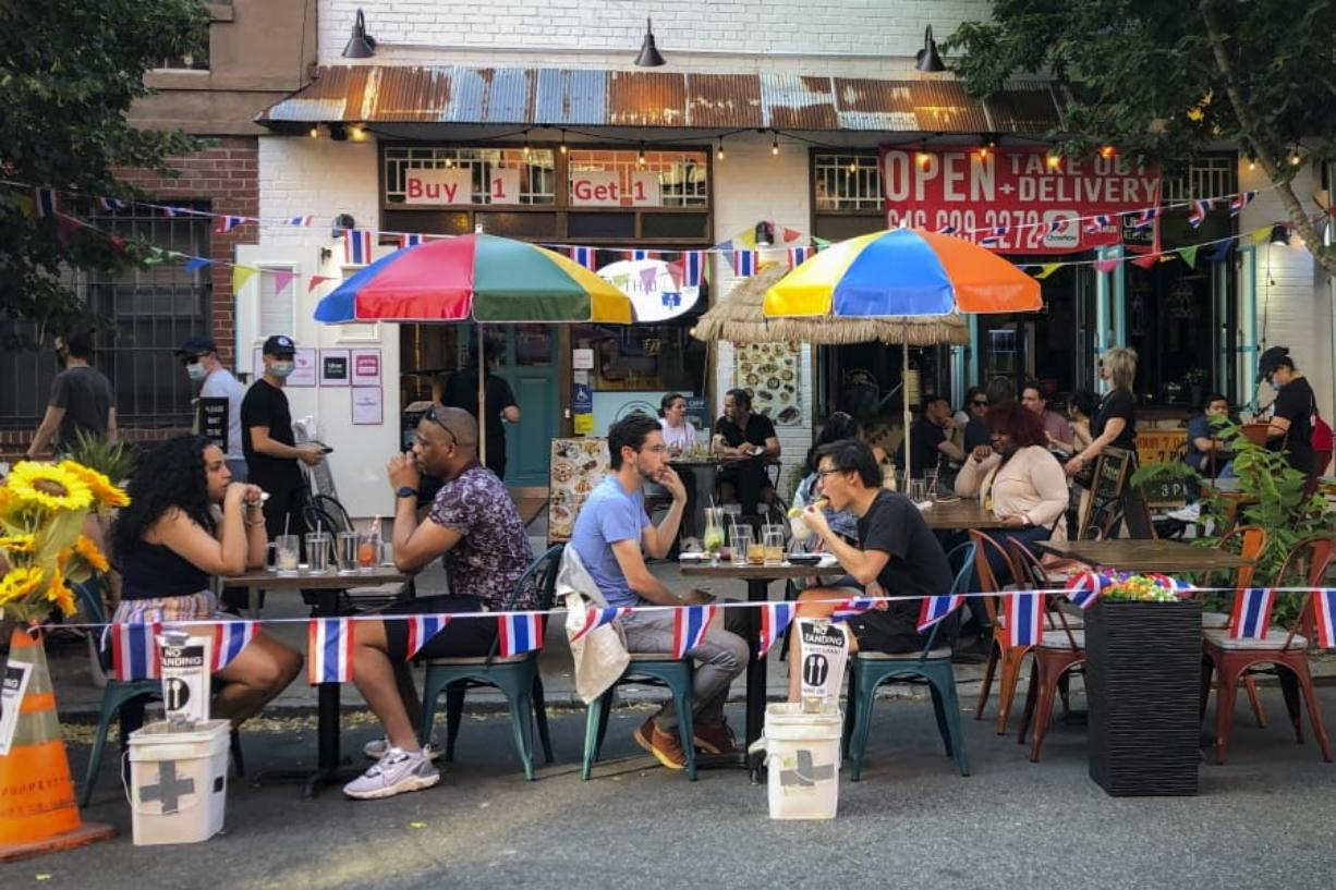 Diners eat al fresco due to COVID-19 concerns in the West Village, Friday, June 26, 2020, in New York. New York City Mayor Bill de Blasio says he's delaying the planned resumption of indoor dining at restaurants in the city out of fear it would ignite a spike in coronavirus infections.