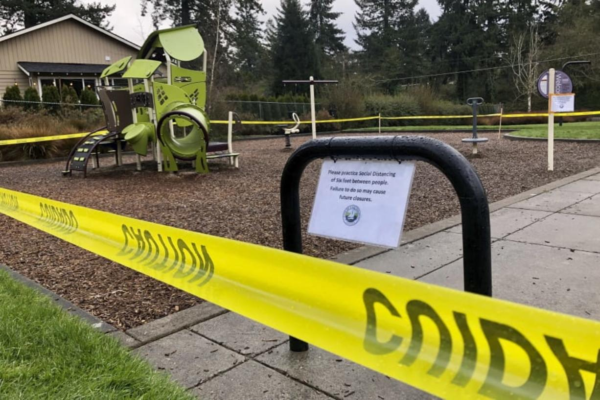 FILE - In this March 24, 2020, file photo, police caution tape surrounds a playground in Lake Oswego, Ore., during the coronavirus outbreak. Oregon health officials reported its second-highest tally of confirmed cases of COVID-19 and five additional deaths on Friday, June 26, 2020, the same day that authorities released new modeling that shows increased transmission of the coronavirus since the state began reopening in mid-May.