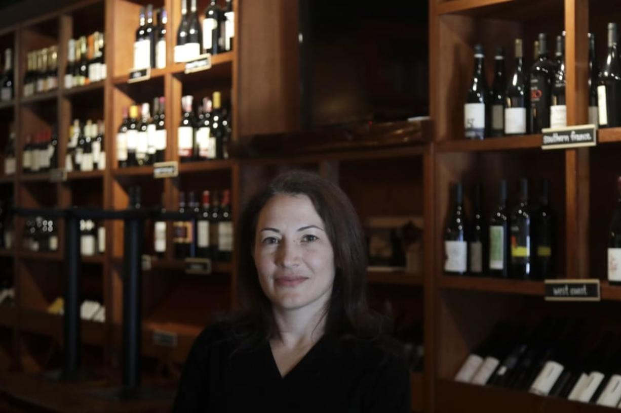 "Sarah Trubnick, owner of The Barrel Room, poses for photos while interviewed at the restaurant during the coronavirus pandemic in San Francisco, Tuesday, July 14, 2020.  The Barrel Room, a San Francisco wine bar and restaurant, cautiously reopened this month, hoping to salvage as much of 2020 as possible.  But as infections climb, Trubnick isn't taking anything for granted. ""We are prepared at any minute to close again,'' she said."