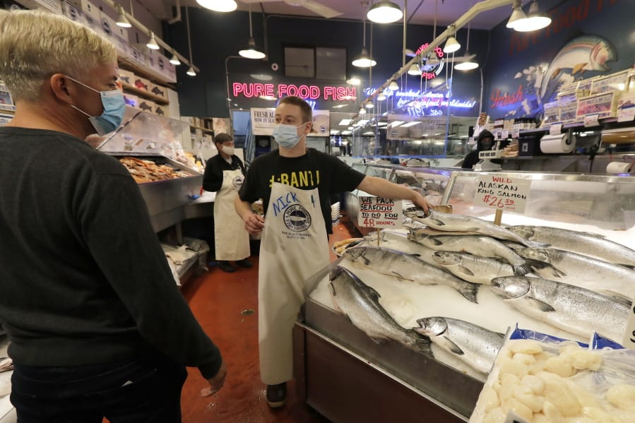 Nicholas Hartmann, center, shows a fish to a customer as he works at the Pure Food Fish Market, Tuesday, July 7, 2020, at Pike Place Market in Seattle.
