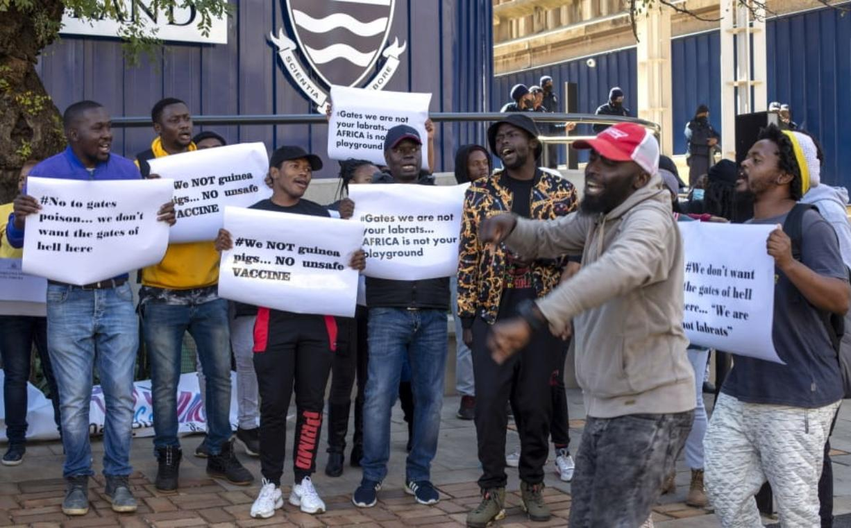 People protest against Coronavirus vaccine trials in Africa, outside the University of the Witwatersrand in Johannesburg, South Africa, Wednesday, July 1, 2020.