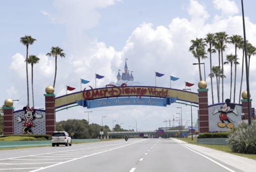 """Cars drive under a sign greeting visitors near the entrance to Walt Disney World, Thursday, July 2, 2020, in Lake Buena Vista, Fla. Despite a huge surge of Floridians testing positive for the new coronavirus in recent weeks, Magic Kingdom and Animal Kingdom, two of Disney World's four parks are reopening Saturday, July 11. When they do, visitors to """"The Most Magical Place on Earth"""" will find new rules in place."""