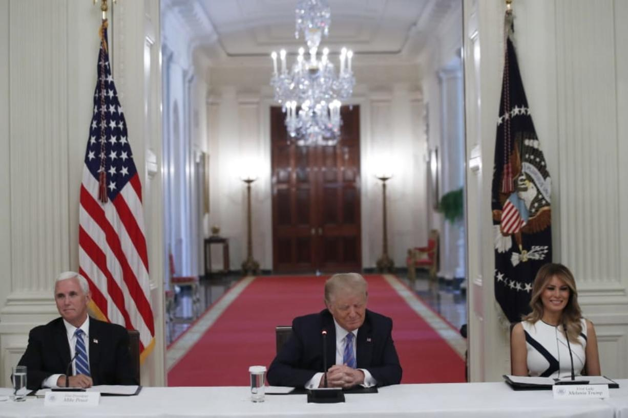 "President Donald Trump, Vice President Mike Pence, left, and first lady Melania Trump, attend a ""National Dialogue on Safely Reopening America's Schools,"" event in the East Room of the White House, Tuesday, July 7, 2020, in Washington."