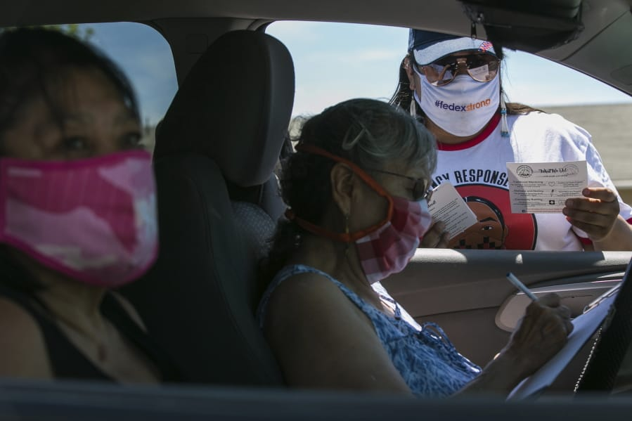In this photo taken on Friday, June 26, 2020, Natasha Scott, right, provides flyer information about the Peacekeeper Society to Patricia Randall, center, and Floraine Gardee, left, during a drive-thru distribution of food and emergency supplies at Harrah City Hall in Harrah, Wash., during the coronavirus pandemic.