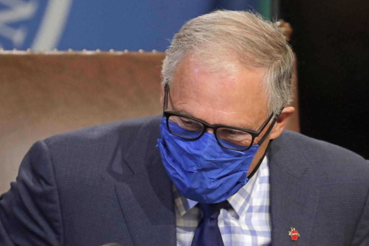 Washington Gov. Jay Inslee wears a face mask as he concludes a news conference, Tuesday, June 23, 2020, at the Capitol in Olympia, Wash. Inslee announced Tuesday that Washington state will require people to wear facial coverings in most indoor and outdoor public settings, under a statewide public health order in response to ongoing COVID-19 related health concerns. (AP Photo/Ted S.