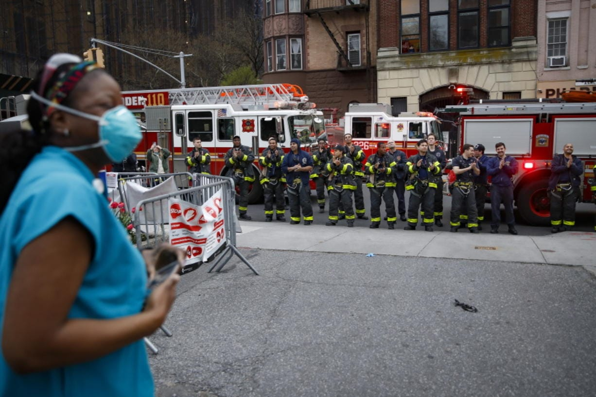 FILE - In this April 14, 2020, file photo FDNY firefighters gather to applaud medical workers as attending physician Mollie Williams, left, wears personal protective equipment due to COVID-19 concerns outside Brooklyn Hospital Center in New York. Essential workers are lauded for their service and hailed as everyday heroes. But in most states nurses, first responders and frontline workers who get COVID-19 on the job have no guarantee they'll qualify for workers' comp to cover lost wages and medical care.