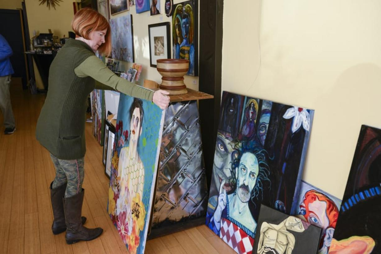 Leah Jackson arranges artwork for a 2017 show on the male form at Angst Gallery in downtown Vancouver. She's closing the gallery to focus on her adjoining Main Street business, Niche Wine Bar.