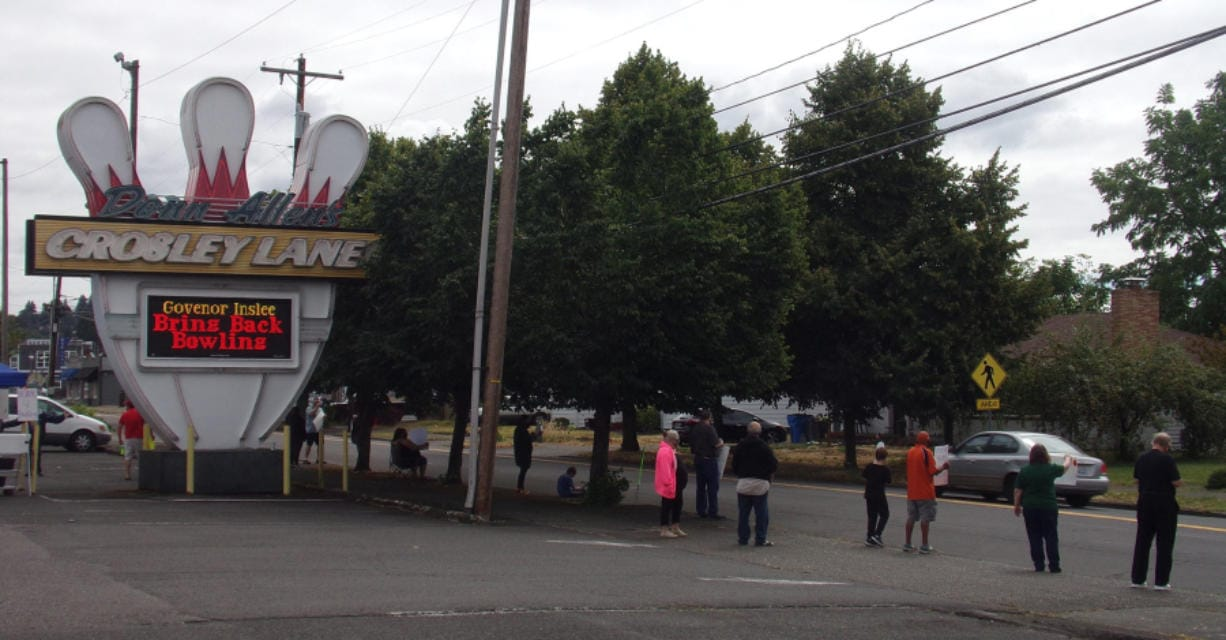 Supporters hold up signs and wave at passing cars in front of Crosley Lanes on Saturday, Aug. 8, 2020, during a Rally for the Alley to help get bowling centers reopened in the state.