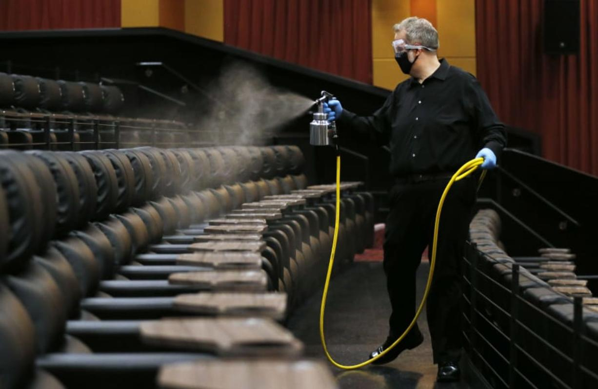 Cinemark West general manager Lindsey Hearn sprays disinfectant on seats in an auditorium the morning before the theater's June 19 reopening.