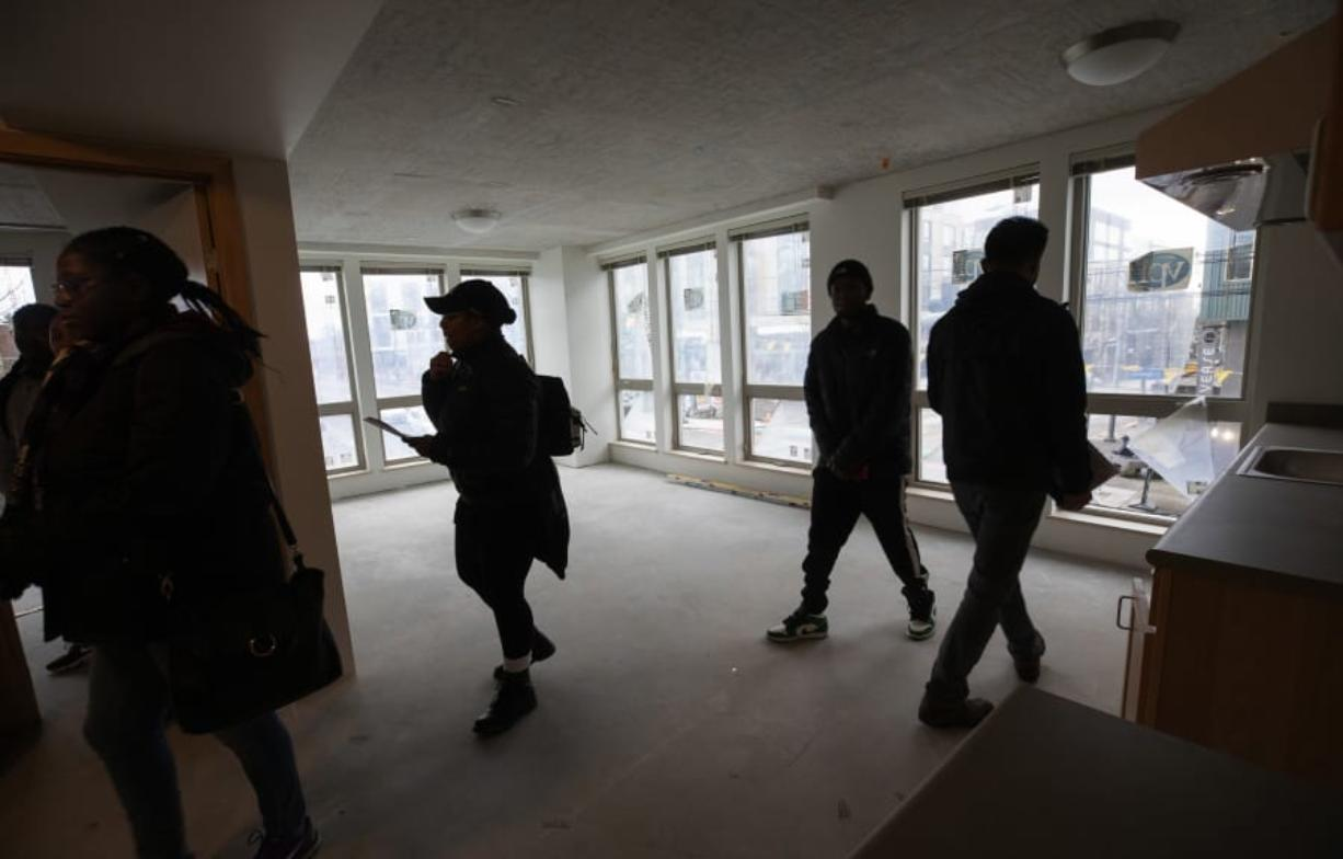 People who have been selected to move into Jackson Heights, a new affordable housing project meant to bring displaced Central District residents back to the Seattle neighborhood, tour the building which is nearly complete on February 1, 2020. (Ellen M.