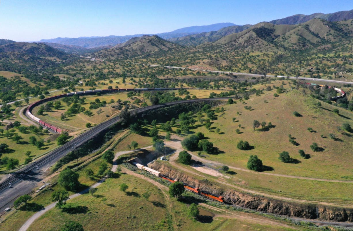 A Burlington Northern Santa Fe Railway train climbs up through the Tehachapi Loop as it heads east out of the Central Valley town of Bakersfield, Calif., on May 2, 2020.