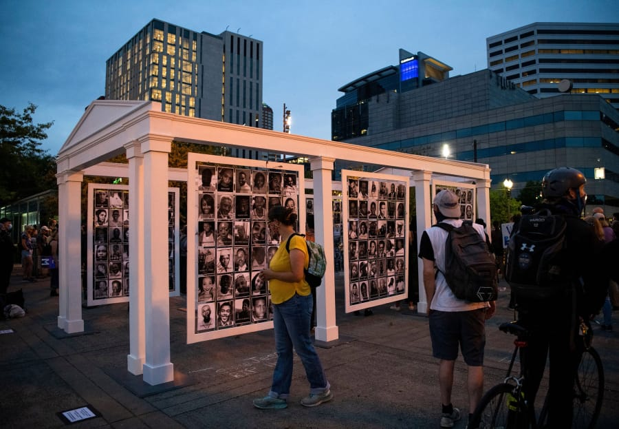 Demonstrators walk by a memorial for 216 Black lives taken by racial violence during a night of protest against racial injustice and police brutality on July 31, 2020 in Portland, Oregon.