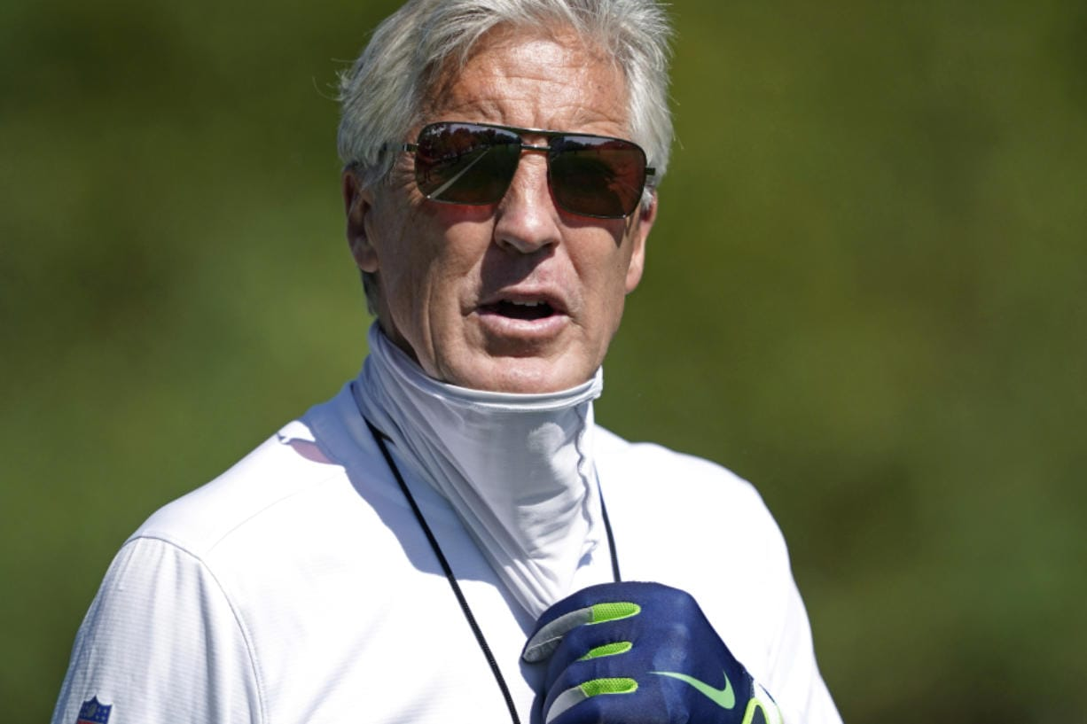 Seattle Seahawks head coach Pete Carroll briefly pulls down his face covering during NFL football training camp, Monday, Aug. 24, 2020, in Renton, Wash. (AP Photo/Ted S.