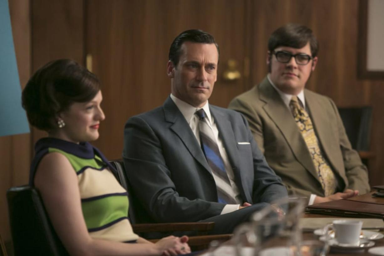 """In this image released by AMC, Elisabeth Moss, from left, Jon Hamm and Rich Sommer appear in a scene from """"Mad Men."""" The final season premieres Sunday at 10 p.m. EST on AMC."""