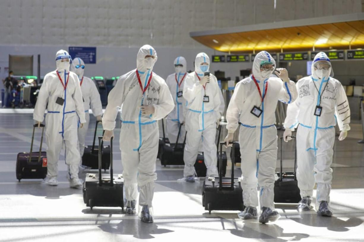 A flight crew in full biohazard suits at Tom Bradley International Terminal at LAX on Friday, May 22, 2020 in Los Angeles, Calif. Qian Lang, the first confirmed case of COVID-19 in Los Angeles, remained the sole patient diagnosed with the virus here for five weeks, passing most of that time in top-secret isolation at Cedars-Sinai Medical Center.