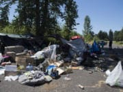 Officer Tyler Chavers stops to check on residents of a homeless encampment in northeast Vancouver in July.