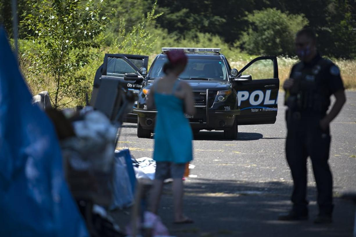 A woman talks with Officer Tyler Chavers as his police vehicle is parked nearby in northeast Vancouver in July.