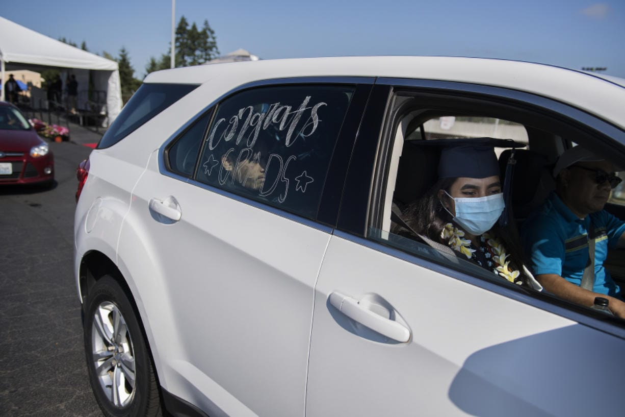 Henrietta Lacks Health and Bioscience High School graduate Cassandra Micah, 18, joins loved ones in her car after walking across the stage to celebrate her accomplishments at McKenzie Stadium on Wednesday morning. Evergreen Public Schools students took part in a drive-thru graduation ceremony, celebrating a year interrupted by the coronavirus pandemic.
