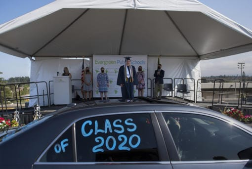 Ilya Panasevich, 18, graduate of Henrietta Lacks Health and Bioscience High School, takes center stage as he pauses to have his photograph taken during a drive-thru graduation ceremony for the class of 2020 at McKenzie Stadium on Wednesday morning. Panasevich was one of 147 graduates from HeLa High School this year, and one of about 1,900 in the Evergreen Public Schools district.