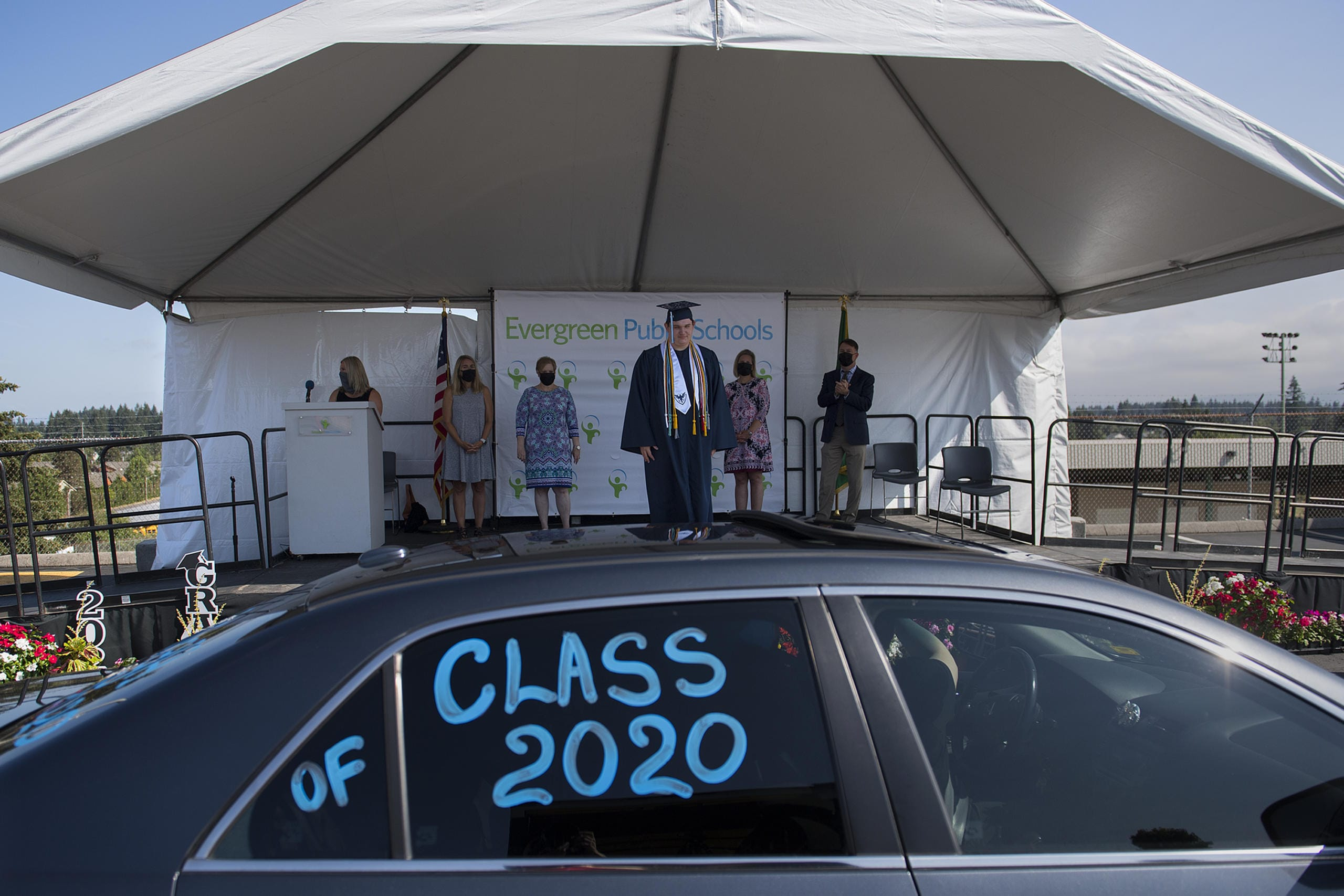 Ilya Panasevich, 18, graduate of Henrietta Lacks Health and Bioscience High School, takes center stage as he pauses to have his photograph taken during a drive-through graduation ceremony for the class of 2020 at McKenzie Stadium on Wednesday morning, August 5, 2020. Panasevich was one of 147 graduates from HeLa High School this year. (Amanda Cowan/The Columbian)
