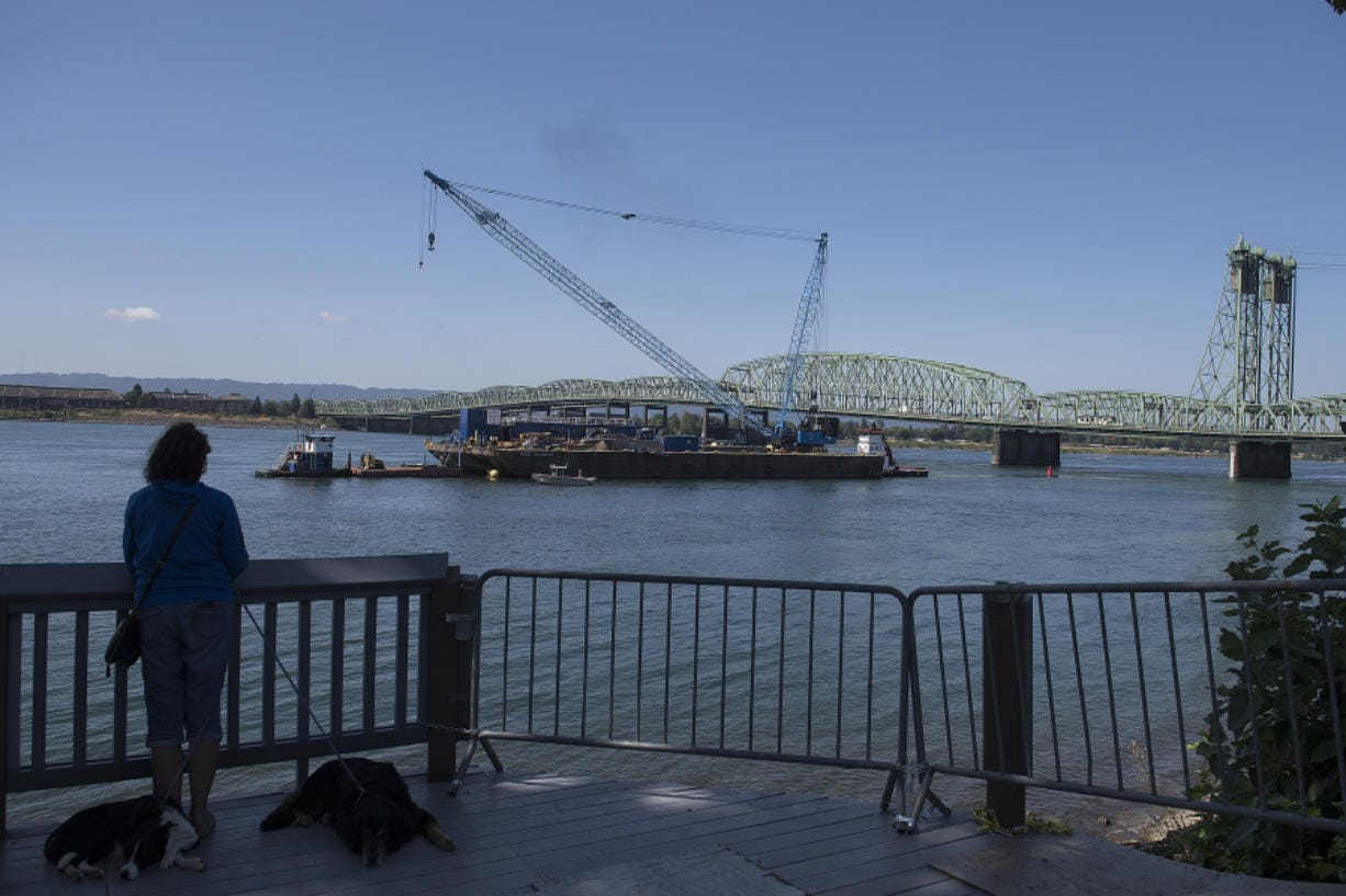 A person watches from the bank of the Columbia River as the trunnion, sheaves and other replacement components for the Interstate 5  Bridge arrive in Vancouver via barge on Tuesday morning.