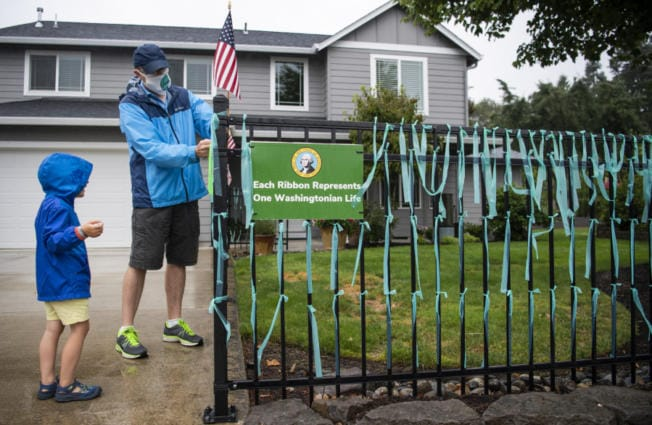 """Vancouver resident Jim Mains and his son Remington, 4, tie ribbons onto the fence outside their home in Vancouver. At the end of March, Mains started this memorial for lives lost to COVID-19 in Washington. """"There's never been a day that we haven't put up ribbons,"""" he said."""