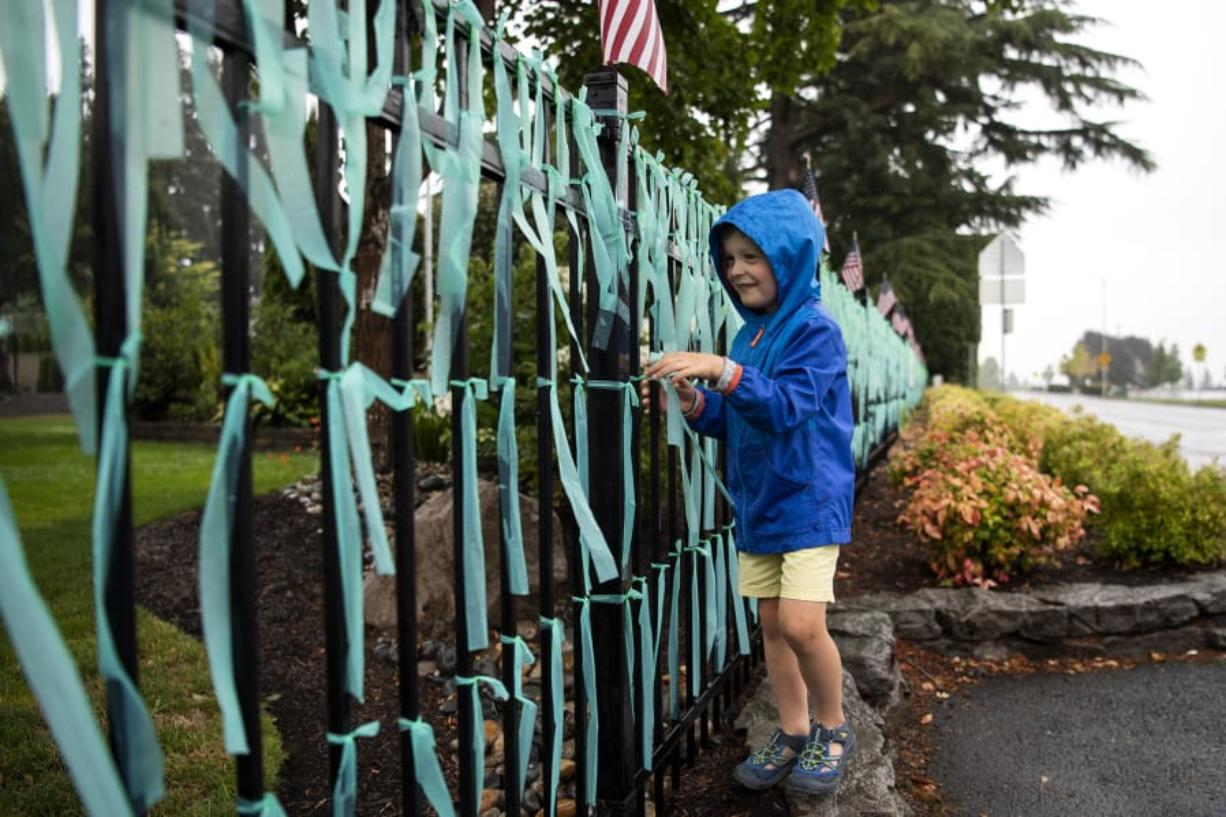 Remington Mains shakes the rain off of ribbons along the memorial outside his home in Vancouver. Each ribbon represents a life lost to COVID-19 in the state of Washington, the number now reaching more than 1,600.