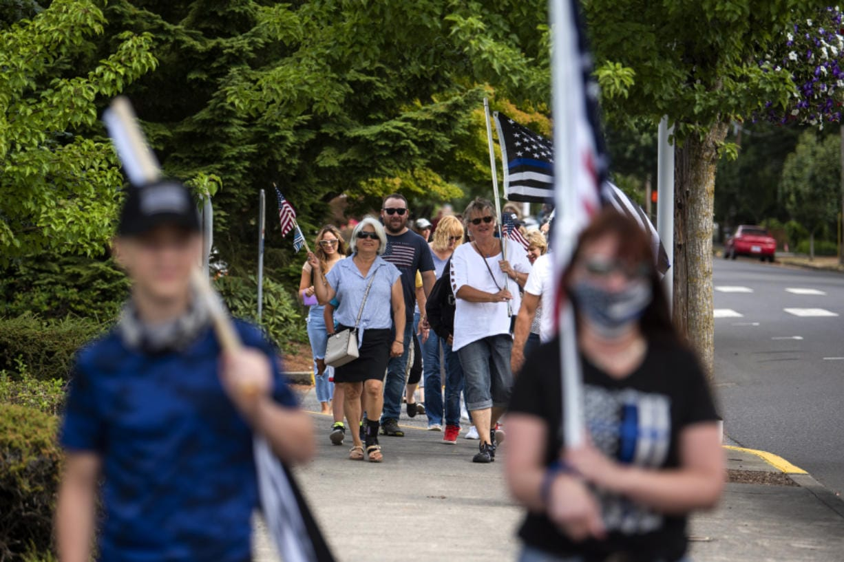 Community members march through downtown Ridgefield during a rally in support of local law enforcement Saturday. About 100 people attended the rally, which was organized by Derek Sommers of Ridgefield.