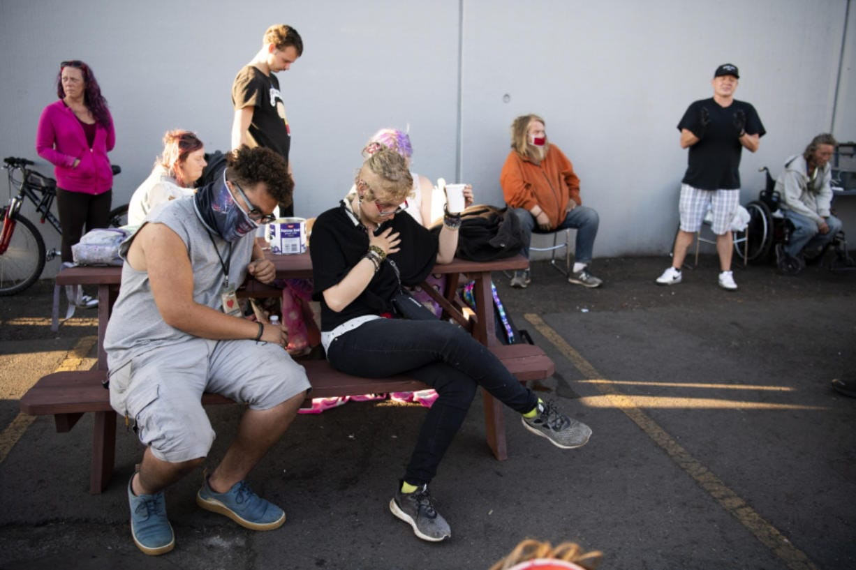 Pastor Brian Norris, in black shirt and cap, leads a prayer before serving a meal at Living Hope Church, where a temporary homeless encampment was set up in early May. It provides shelter, showers, snacks and restrooms to people without homes during the pandemic.