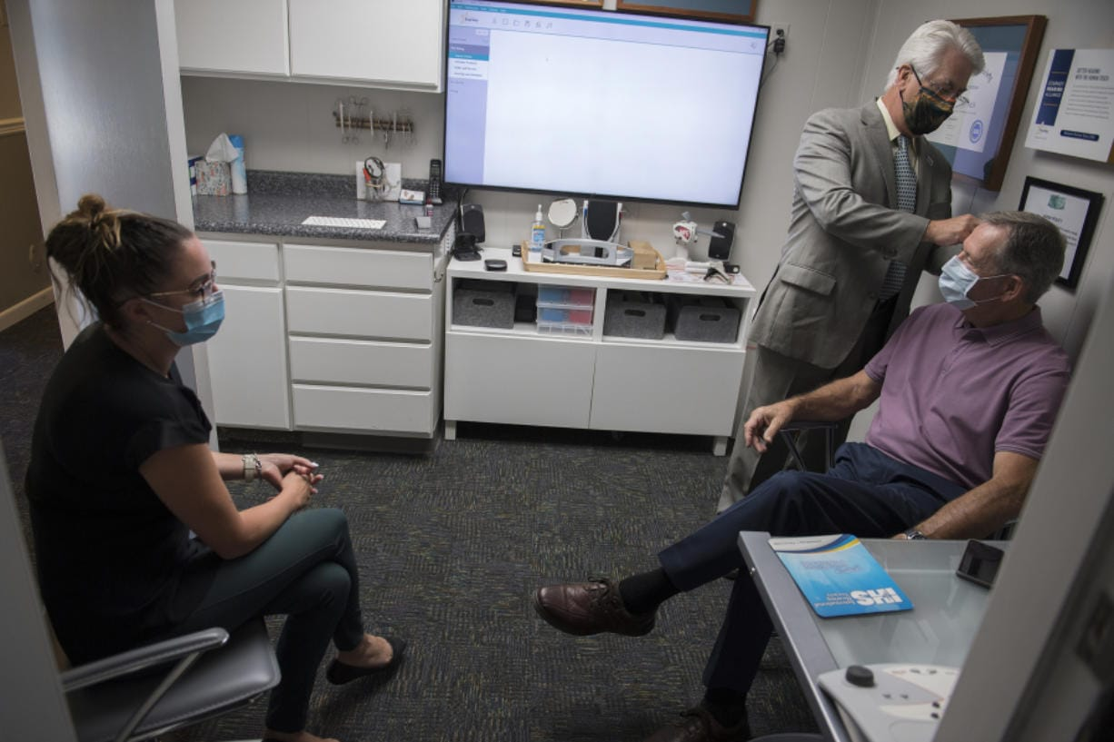 Elizabeth Miller, from left, current owner of Hearing by Design, looks on as consultant Rick Giles works with Don Stose, Mayor of Ridgefield, as he programs Stose's hearing aid response during an appointment.