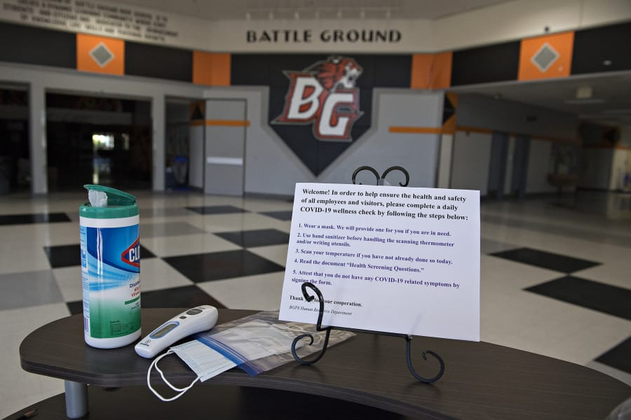 A station is set up to screen visitors to Battle Ground High School for symptoms of COVID-19, as seen on Tuesday morning. Districts like Battle Ground are eligible for coronavirus relief funds to help cover the cost of responding to the pandemic, including the purchase of personal protective equipment and technology.