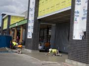 Construction workers bring a new Grocery Outlet store to life at Evergreen Plaza on Wednesday. The location is a former Salvation Army thrift store.