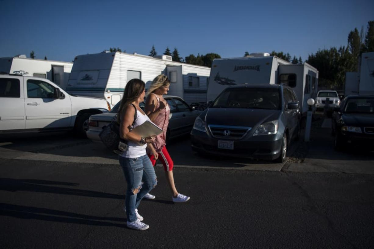 Michele Houston, left, and Cindy Genschorck, right, walk through Hazel Dell RV Park, formerly known as Vancouver RV Park, to talk with tenants about an upcoming online meeting to discuss recent rent increase notices.