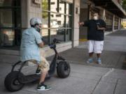 Customer Mark Shelton, left, adjusts his helmet as Zoot Scoot co-owner Jason Adams gives him a safety breakdown outside Zoot Scoot in Vancouver. The electric scooters sales and rental shop opened in June and quickly sold out of inventory. The shop will be getting a new batch of scooters this week for both retail and rental.