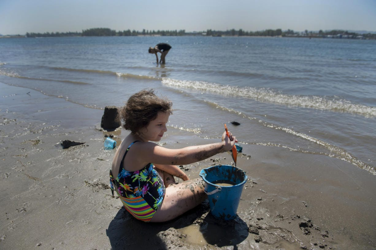 Vancouver resident Heidi Zeigler, 8, cools off in the water while playing in the sand with her mom along the sun-soaked shoreline of the Columbia River on Friday afternoon. Heidi was one of a handful of visitors to the scenic area as residents sought refuge from the high summer temperatures. Forecasts anticipate that high temperatures could reach triple digits over the weekend.