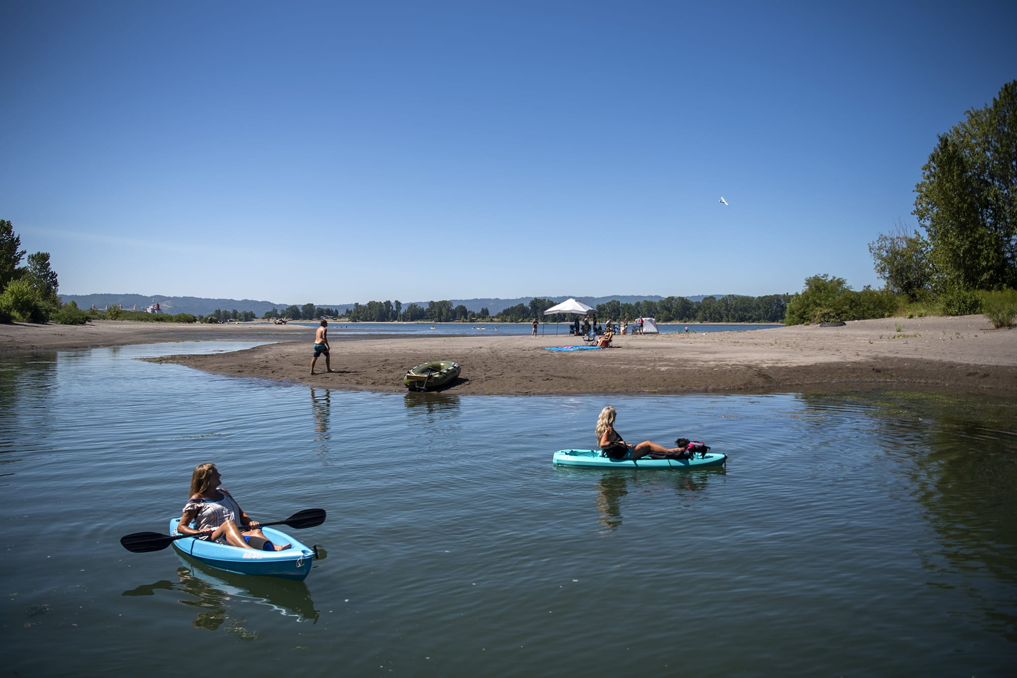Bev Kadow, left, and her friend Kelly Kopp, right, watch an airplane fly above as they kayak along an offshoot of the Columbia River in Vancouver on August 15, 2020. An excessive heat warning has been issued throughout the weekend until Sunday evening, with temperatures around 100 degrees.  (Alisha Jucevic/The Columbian)