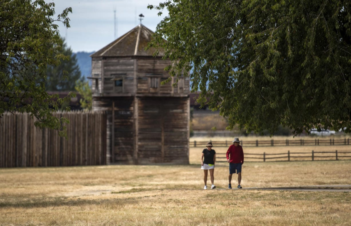 Tami Nesburg, left, and her co-worker Randy Krenelka take a walk during their lunch break Thursday at Fort Vancouver National Historic Site. Attractions such as the visitor center, reconstructed Fort Vancouver and Pearson Air Museum are closed, but the parking lots and walking paths are open.