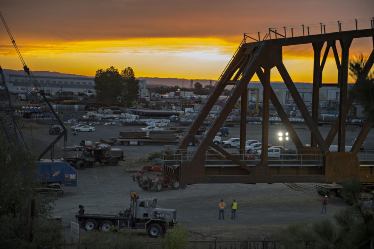 The sun sets as crews move the BNSF railroad truss bridge to a barge on Monday evening. The bridge will be floated about 60 miles up the Columbia River to Drano Lake, where it will be installed to replace a century-old bridge on the rail line.