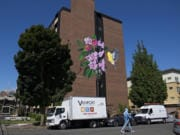 A pedestrian strolls past a new, colorful mural on the east side of Van Vista Plaza Assisted Living in downtown Vancouver on Tuesday morning. Vancouver Housing Authority commissioned the painting as part of its ongoing renovation of the 60-unit apartment building for low-income seniors at 410 W. 13th St.