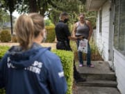 Vancouver Deputy Fire Marshal LeMont Lucas, center, shows a brief fire-safety video to Katie Jefferson outside her home Saturday morning. Firefighters and volunteers with the Vancouver Fire Department canvas Vancouver neighborhoods every week to disseminate fire safety information and hand out souvenir reminders.