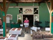 Above, a woman carries a box of produce outside Joe's Place Farms, which sells more than 25 different fruits and vegetables.